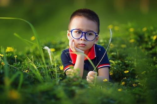Kind mit blauer Brille im Gras